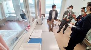 患者とガラス越しにやりとりできる病室を見学するFICネットのメンバーら=5月29日、福井県小浜市の公立小浜病院