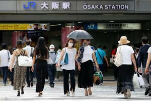 日傘を差し、JR大阪駅前を歩く人たち=4日午後