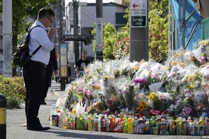 児童らが殺傷された現場付近に供えられた花の前で手を合わせる男性=5月30日午前、神奈川県川崎市多摩区