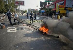 デモ隊が燃やしたバリケードを撤去する警官=12日、インド北東部グワハティ(ロイター=共同)