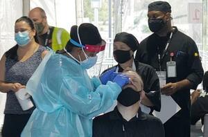 18日、米フロリダ州で新型コロナウイルスの検査を受ける人ら(UPI=共同)