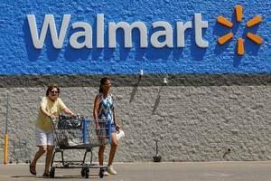 米ウォルマートのロゴと買い物客=7月、ペンシルベニア州(ロイター=共同)
