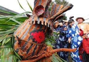 赤土を塗った棒を手に、人々を追い回すボゼ=6日午後、鹿児島県・トカラ列島の悪石島