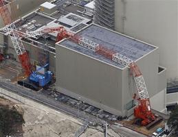 関西電力高浜原発2号機の燃料取り扱い建屋に向かって倒れたクレーン=21日午後、福井県高浜町(共同通信社ヘリから)
