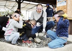 化石の発見を目指してハンマーを振るう参加者=19日、福井県勝山市の長尾山総合公園