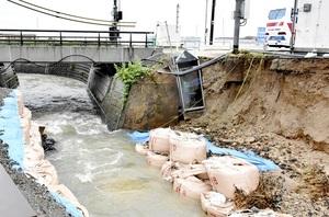 増水により仮設の盛り土がえぐられ、公衆電話ボックスが滑り落ちた馬背川=7月6日午前8時15分ごろ、福井県美浜町竹波