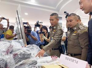 日本人の男15人を含む特殊詐欺グループから押収した証拠品について説明するタイ警察の幹部ら=22日、バンコク(共同)