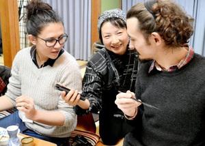 スマホの翻訳アプリを使ってフランス人のツアー客とコミュニケーションを取る従業員(中央)=21日夜、福井県小浜市阿納