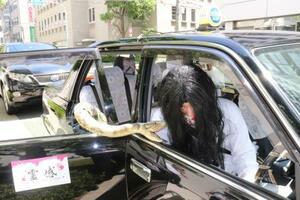 未来都の「霊感タクシー」。白装束姿の運転手が接客する=21日、大阪市