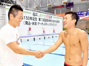 恩師の内藤直樹さん(左)に健闘をたたえられ、握手する新良貴優選手=9月17日、石川県金沢市の金沢プール