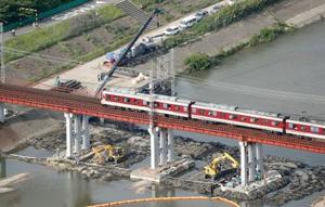 復旧作業を終え、大阪府の大和川に架かる橋上を通過する近鉄南大阪線の電車=26日午後(共同通信社ヘリから)