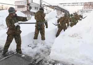 追加要請を受け、大雪で埋もれた「福井鉄道」の線路の除雪をする自衛隊員=9日午後、福井市