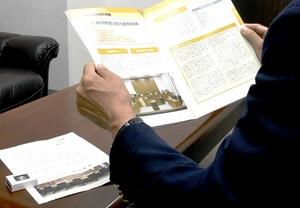 裁判員制度を紹介する冊子を持ち経験を語る男性。経験は自らの人生史に深く刻まれた=福井県福井市内