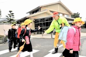 交通安全に気を配りながら、児童のあいさつや笑顔を引き出そうと外国語で話しかける水野昭さん=4月、福井市浅水二日町