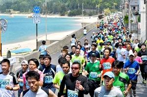 美浜・五木ひろしマラソンで、美しい海岸沿いを駆け抜ける5キロの部の出走者=14日、福井県美浜町竹波