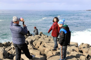 東尋坊で記念撮影する香港の家族=28日、福井県坂井市