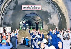 新北陸トンネルの貫通を祝い、万歳三唱する関係者。奥は南越前町方面=7月10日、福井県敦賀市葉原