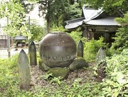 直径約1メートルの機雷と、それを囲むように置かれた四つの砲弾=福井県鯖江市の劔神社