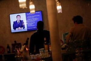 マクロン仏大統領のテレビ演説を見る人々=28日、パリ(ロイター=共同)