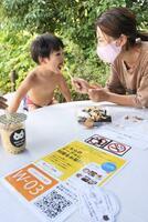 「河川環境楽園 オアシスパーク」の屋外テーブルで、QRコードを使い注文したおやつを食べる親子=9月、岐阜県各務原市