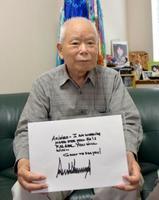 トランプ米大統領からの手紙のコピーを手に、取材に応じる有本明弘さん=16日、神戸市