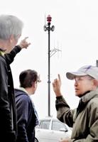 弾道ミサイル発射を知らせる防災行政無線スピーカー(奥)。福井市北体育館ではバウンドテニス大会が開かれており、福井県内外の選手たちが館外に出て耳を傾けた=14日午前11時10分ごろ