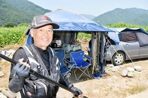 尺アユを狙い、九頭竜川のそばで寝泊まりする矢口勝利さん。テントや車には冷蔵庫や調理器具がそろっている=福井県勝山市内