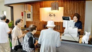 営業再開で次々とフロントに訪れる入浴客=25日、福井市佐野町の「天然温泉佐野温泉 福の湯」別館