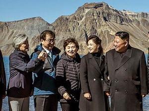 中朝国境にある白頭山を訪問し、指でハートの形を作る方法を示す韓国の康京和外相(左端)を見る北朝鮮の金正恩朝鮮労働党委員長(右)と李雪主夫人(同2人目)=20日(韓国大統領府提供・共同)