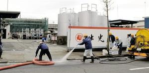 漏れた重油の回収や清掃を行う業者ら=27日午後2時45分ごろ、福井市志比口1丁目