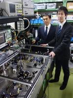 東京大の古沢明教授(左)らが開発した量子コンピューターの一部となる装置=15日、東京都文京区