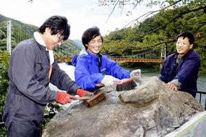 完成した歌碑を磨く和泉地区の住民たち=9月22日、福井県大野市下半原