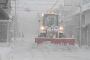 吹雪の中、市街地の道路を除雪する車両
