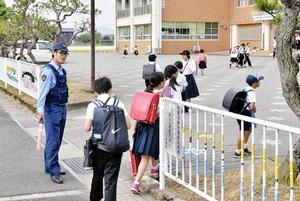 警察官に見守られながら登校する児童=6月5日午前7時40分ごろ、福井県鯖江市大倉町