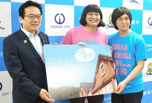 渕上隆信市長(左)から敦賀ふるさとサポーターに委嘱されたハイキングウォーキングの2人=15日、福井県敦賀市役所