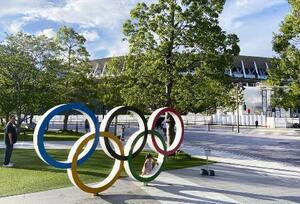 五輪マークのモニュメントと東京五輪の開会式が行われる国立競技場(奥)=東京都新宿区