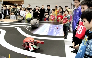 優勝した結川陽登君(右手前)と多田葵一君(右手前から2人目)のロボット。センサーでコースの白と黒の部分を読み取り、8本足で歩いている=26日、福井市のハピリン