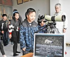 望遠鏡をのぞいて卵を守るコウノトリを観察する児童=3日、福井県越前市の商工会白山支所