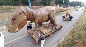 倉庫に向かって国道158号を移動する恐竜親子のモニュメント=11月25日、福井県大野市板倉