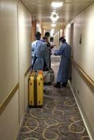 4日、クルーズ船「ダイヤモンド・プリンセス」の客室を巡回する検疫官とみられる担当者(乗客提供)