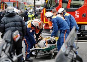 12日、パリ中心部のパン屋で起きた爆発で担架に乗せられた女性(共同)