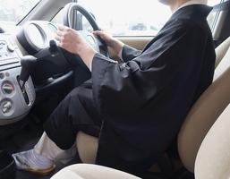 青切符を切られた男性と同様の白衣と布袍を着て車の運転席に座る僧侶。仏教界で法事のため僧衣で運転する機会は日常的にあるという=福井県福井市