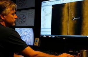 米太平洋ハワイ諸島北西の環礁で第2次大戦中に沈んだ軍艦のソナー画像を見る調査チームのメンバー。旧日本海軍の空母かどうかは不明=20日(AP=共同)