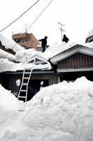 一人暮らし高齢者世帯の屋根雪を下ろす業者=10日正午ごろ、福井市松本3丁目