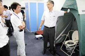 マンホールトイレの仕組みについて説明を受ける参加者(左)=6日、福井市のアオッサ