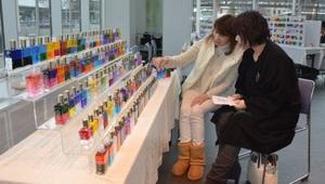 オーラソーマの説明を受ける体験会の参加者(手前)=14日、福井市のアオッサ