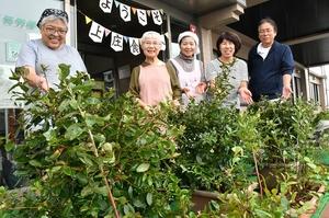 ブルーベリーの鉢植えを前に笑顔を見せる「結こっさの会」のメンバーら=10月19日、福井県大野市の上庄公民館