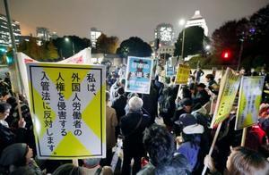 国会前でプラカードを掲げ、入管難民法や水道法の改正に抗議する人たち=6日夜