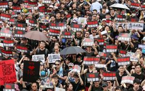 中国本土への容疑者引き渡しを可能にする「逃亡犯条例」改正案の撤回を求めデモ行進する人たち=16日、香港(共同)