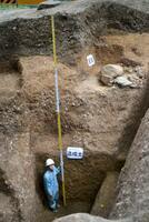発掘調査で見つかった深さ3・3メートル以上の造成土。右上は武家屋敷とみられる石垣の一部=20日午後、京都市伏見区